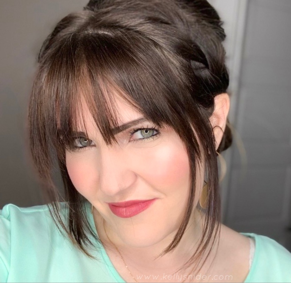 How to Contour in 5 Easy Steps by popular beauty blogger and top artist with Maskcara Beauty, Kelly Snider; Image of Brunette woman with bangs and read lips wearing Maskcara Beauty's iiiD foundation.