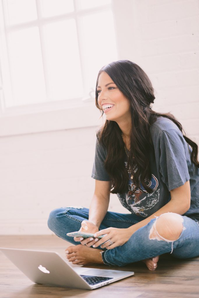 Image of Cara Brook, Founder and CEO of Maskcara Beauty, sitting on floor, cross-legged, and smiling with phone in hand and laptop in front of her.