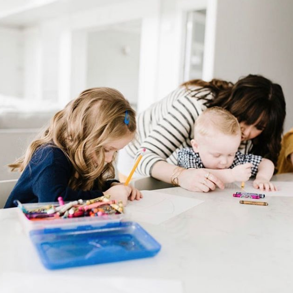 Stay at Home Makeup by popular Utah beauty blogger, Kelly Snider: image of a woman coloring with her kids at their kitchen island counter.