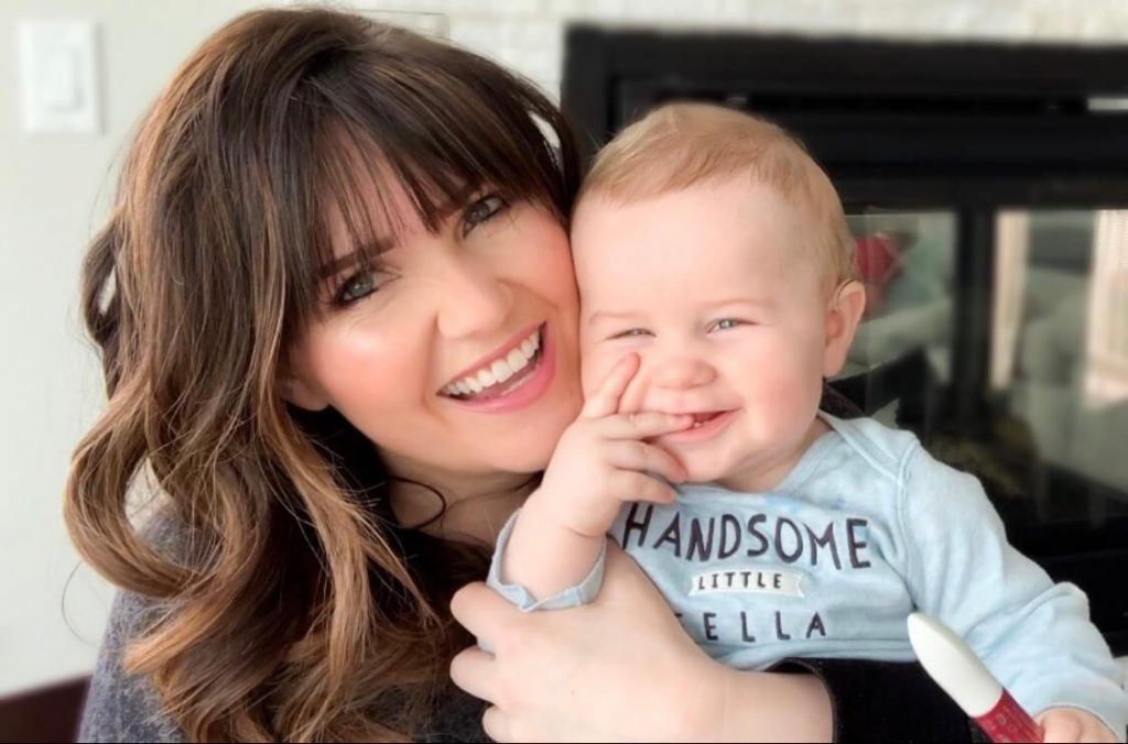 Popular Utah Blogger and Independent Maskcara Artist, Kelly Snider addresses MLM jobs for stay-at-home moms; image of smiling mom holding a smiling baby.