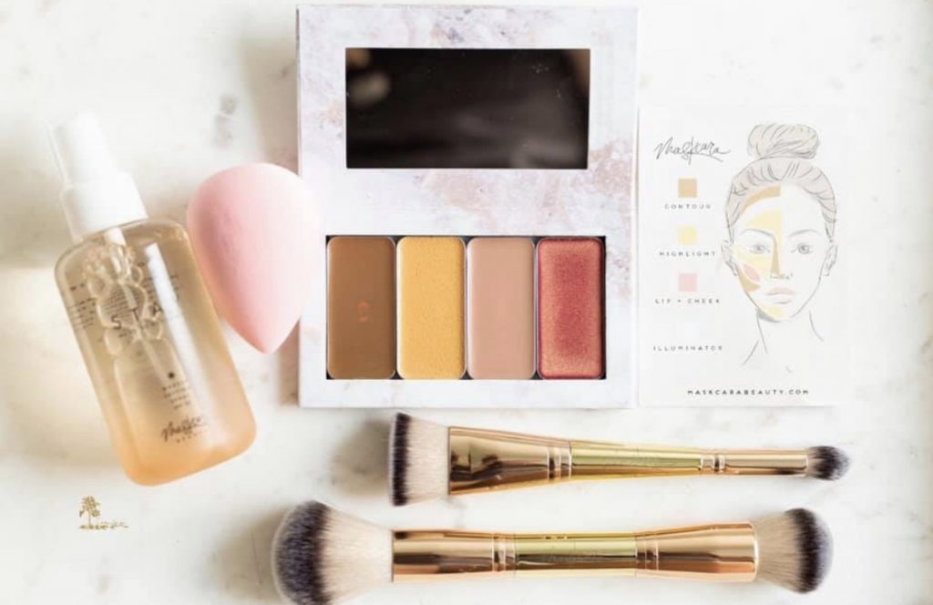 How to Earn Free Makeup from Maskcara beauty by popular blogger and top independent artist for Maskcara Beauty, Kelly Snider; image of a Maskcara Beauty iiiD Foundation compact and makeup tools.