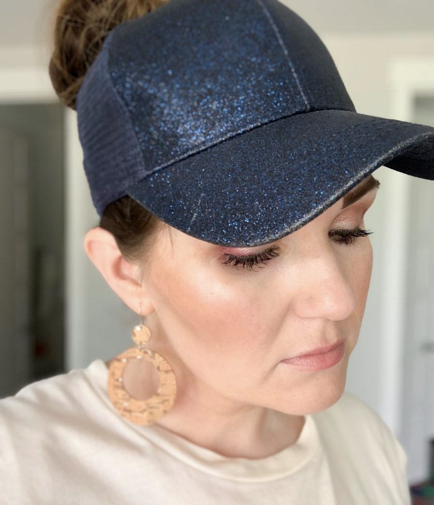 Messy Bun Hats - The best fifth day hair hack by Popular Utah Blogger and Top Maskcara Beauty Artist, Kelly Snider; image of woman wearing a navy blue sparkly messy bun hat with cork hoop earrings.