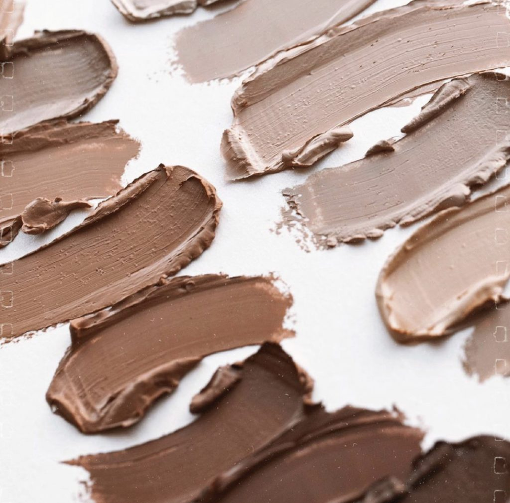 Popular beauty blogger and Seint artist, Kelly Snider, discussing cream makeup for beauty on a budget; Swatches of Seint cream makeup.